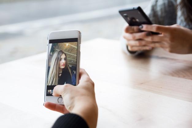Mulheres novas bonitas que usam seu telefone móvel no café.
