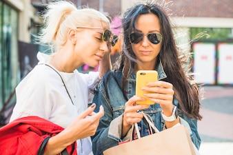 Mulheres, óculos de sol, usando, smartphone