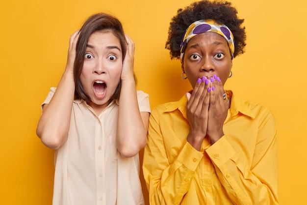 Mulheres olham assustadas para a câmera notam algo assustador com olhos esbugalhados perto uma da outra no amarelo