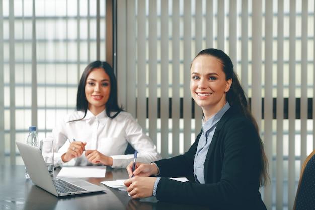 Mulheres, olhar, documentos financeiros, em, laptop, tabela