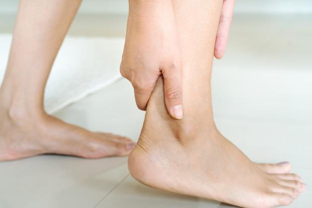 Mulheres perna lesão no tornozelo / doloroso, as mulheres tocam a perna do tornozelo dor