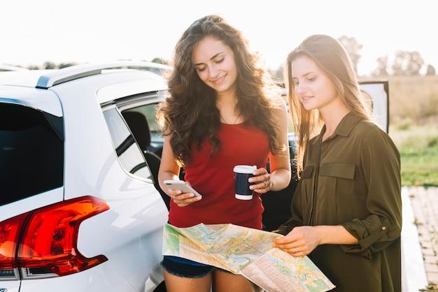 Mulheres perto de carro com roteiro