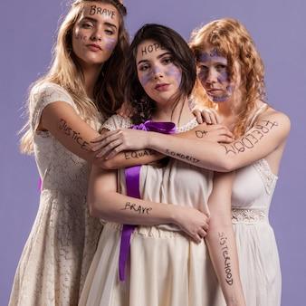 Mulheres pintadas com palavras posando enquanto abraçando