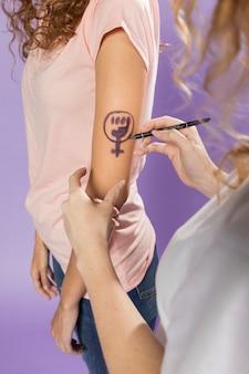 Mulheres pintando o símbolo do feminismo no braço
