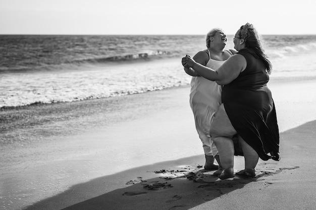 Mulheres plus size dançando na praia se divertindo durante as férias de verão - mulheres curvilíneas rindo juntas - corpo acima do peso e conceito de felicidade - edição em preto e branco