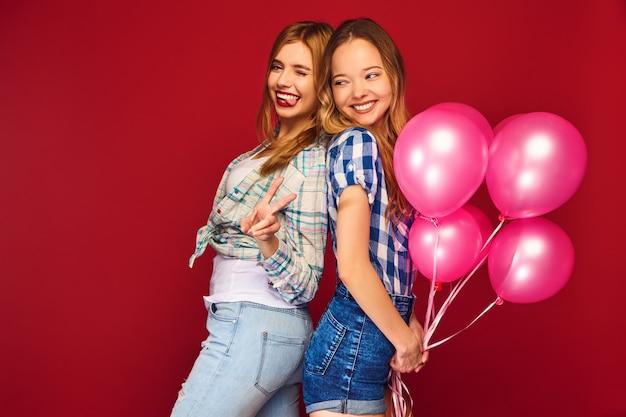 Mulheres posando com grande caixa de presente e balões rosa