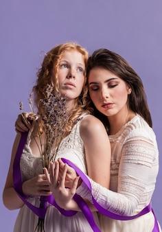 Mulheres posando com um buquê de lavanda e fita