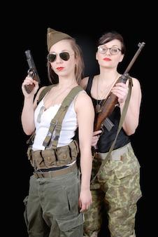 Mulheres posando em armas e uniformes militares
