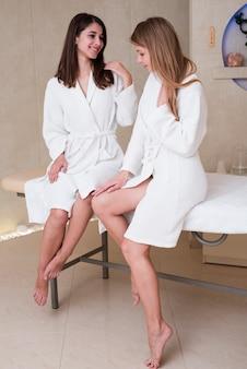 Mulheres posando em roupões de banho junto à mesa de massagem