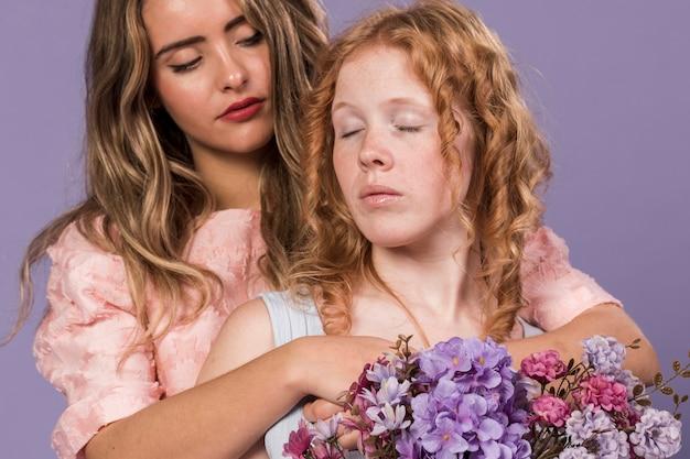 Mulheres posando enquanto abraçando e segurando um buquê de flores