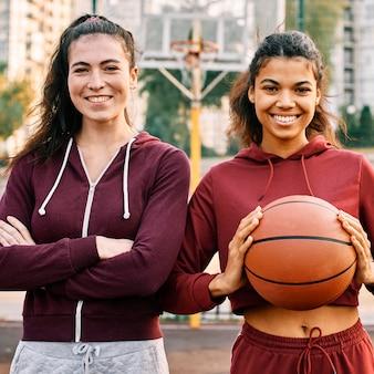 Mulheres posando junto com uma bola de basquete