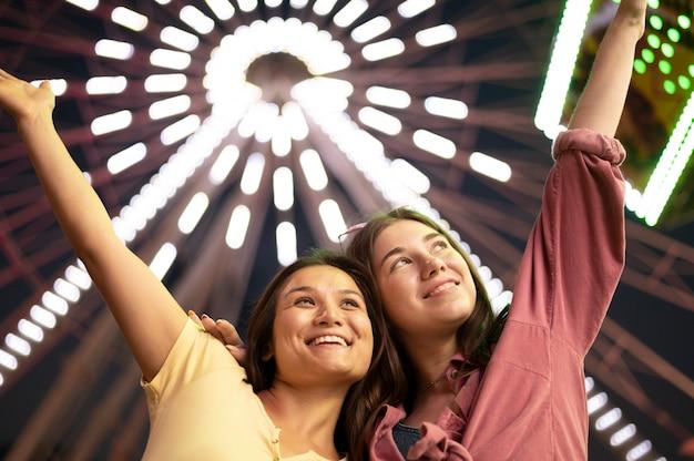 Mulheres posando no parque de diversões ao lado da roda gigante