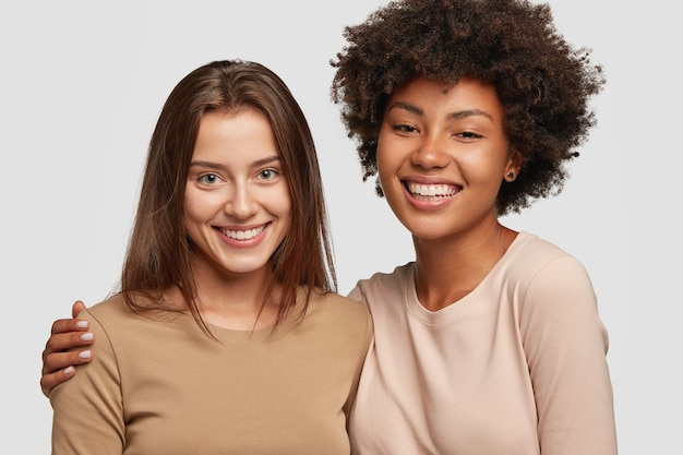 Mulheres positivas de diferentes raças ficam próximas umas das outras, têm um abraço caloroso, um sorriso agradável, relacionamentos amigáveis
