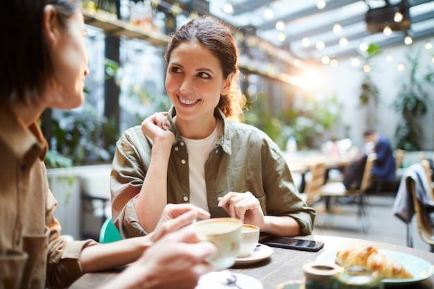 Mulheres positivas que discutem as últimas notícias no café