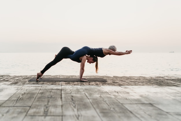 Mulheres praticando acro yoga asana perto do mar no nascer do sol
