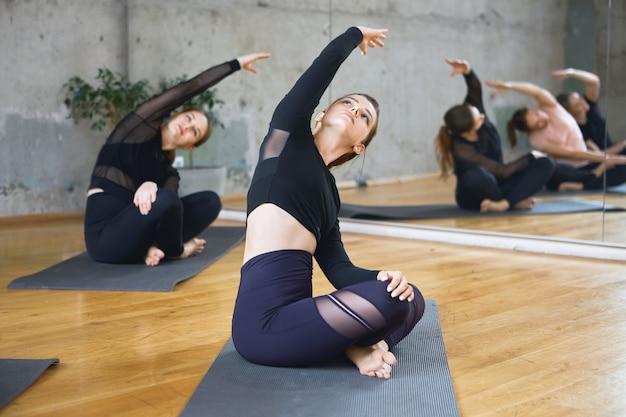 Mulheres praticando alongamento em pose de lótus em esteiras.