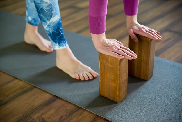 Mulheres praticando ioga alongamento usando blocos de madeira com as mãos, exercício para flexibilidade da coluna e ombros