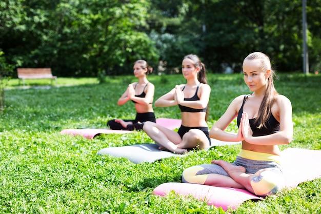Mulheres praticando ioga no parque.