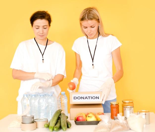 Mulheres preenchendo caixas de doação com alimentos