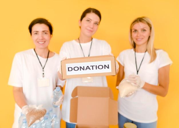 Mulheres preparando caixas com comida para doar
