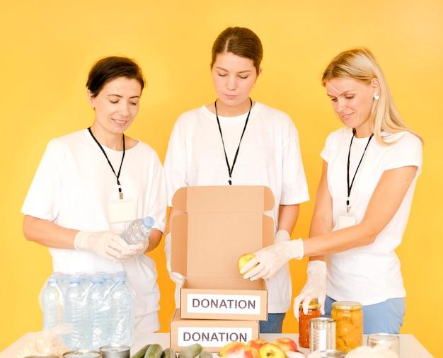Mulheres preparando caixas para doar para o dia da comida