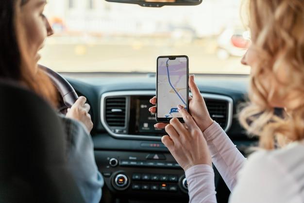 Mulheres procurando um local no mapa do telefone