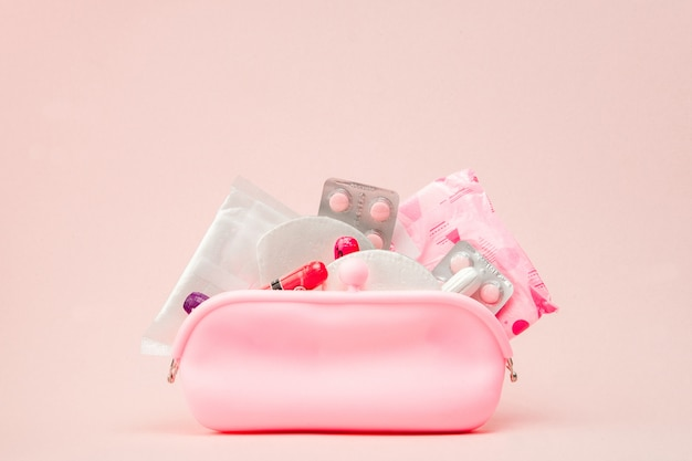 Mulheres produtos de higiene íntima - absorventes e tampões na parede rosa, cópia espaço. conceito do período menstrual. vista superior, configuração plana, cópia espaço