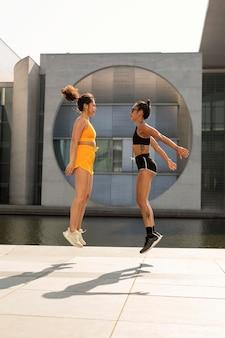Mulheres pulando juntas em tiro completo