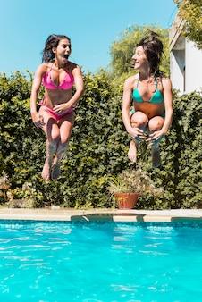 Mulheres, pular, em, piscina, e, olhando um ao outro
