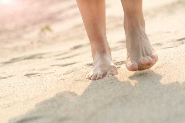 Mulheres que andam com os pés descalços na natureza branca da areia na praia. viagem de verão
