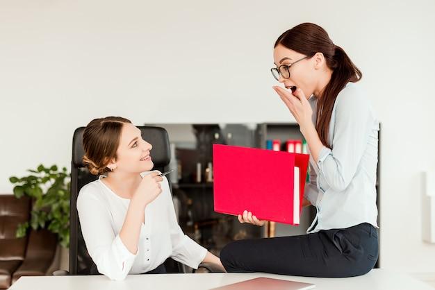 Mulheres que compartilham notícias no escritório no local de trabalho