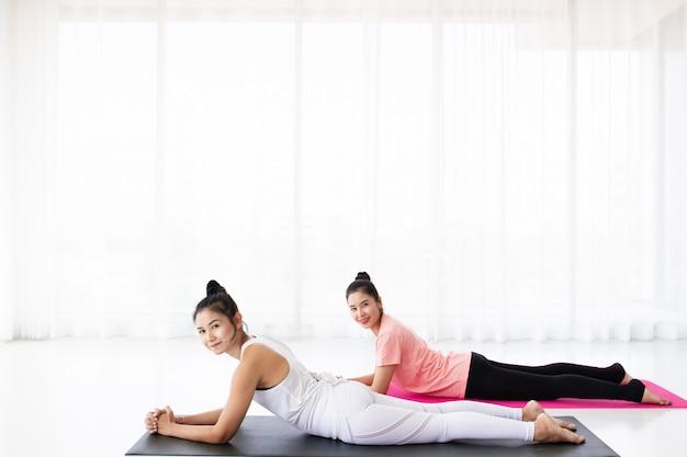 Mulheres que fazem exercícios de ioga juntos