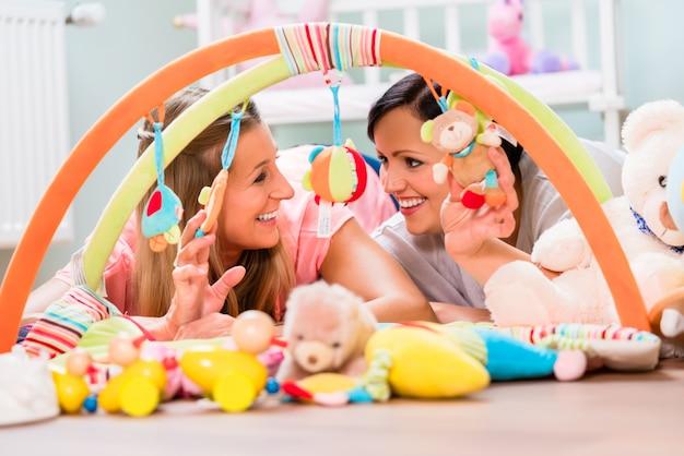 Mulheres que fornecem o quarto do bebê que prepara a barra do jogo para sucklings