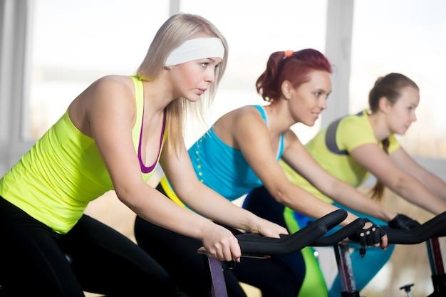 Mulheres que montam uma bicicleta