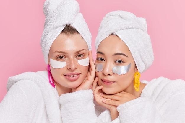 Mulheres que passam por procedimentos de beleza após tomar banho ficam próximas umas das outras, têm pele saudável, rosto limpo, usam roupões de banho e toalhas nas cabeças isoladas na parede rosa
