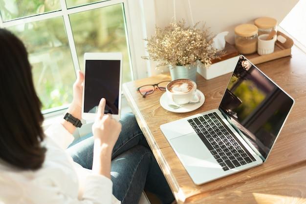 Mulheres que trabalham com ipad e laptop no café