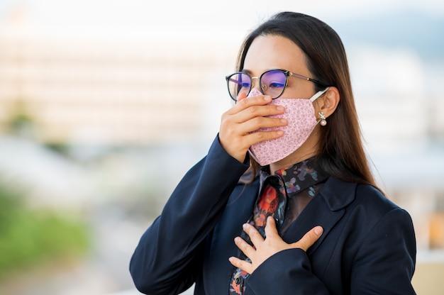 Mulheres que trabalham com máscaras, tosse e dor de garganta devido a uma infecção por vírus