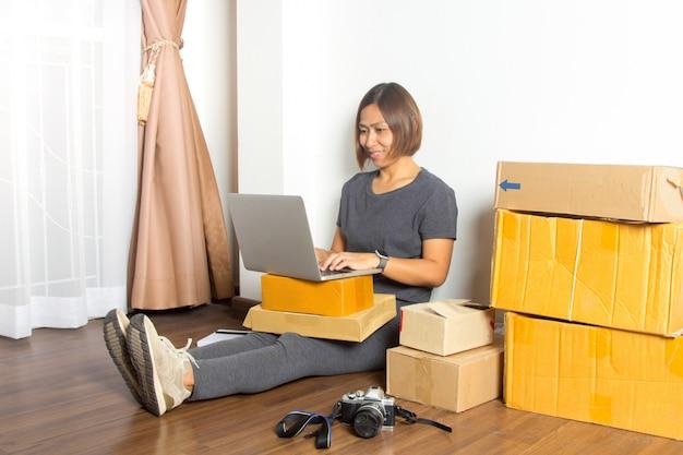 Mulheres que trabalham o computador portátil de casa no assoalho de madeira