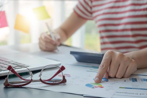Mulheres que usam calculadora e laptop para calcular finanças, impostos, contabilidade