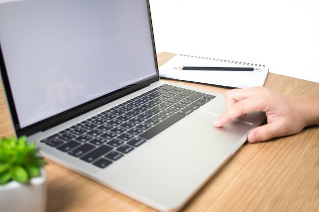 Mulheres que usam laptops com telas brancas em branco em modernas mesas de madeira.