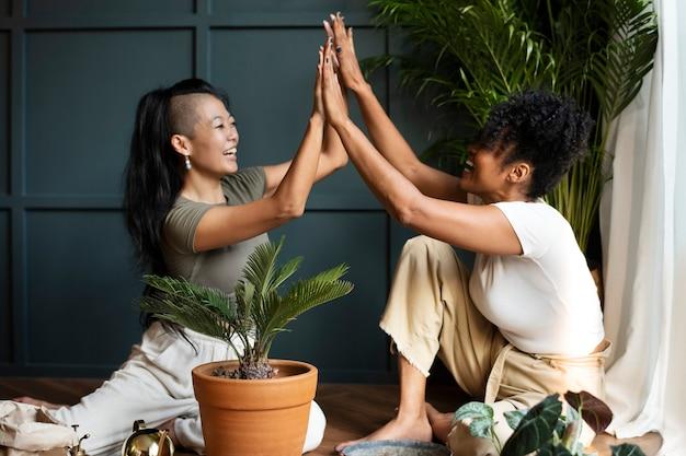 Mulheres repotting plantas em casa no novo normal