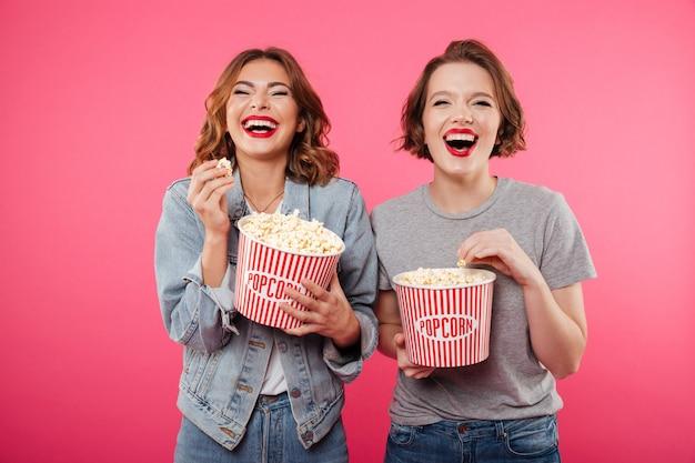 Mulheres rindo alegres comendo filme de relógio de pipoca.