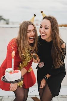 Mulheres rindo em vestidos vermelhos e pretos, segurando o bolo de aniversário e a taça de champanhe