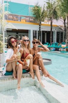 Mulheres rindo usam óculos escuros elegantes posando juntos no resort. senhoras brancas relaxando na piscina e sorrindo.