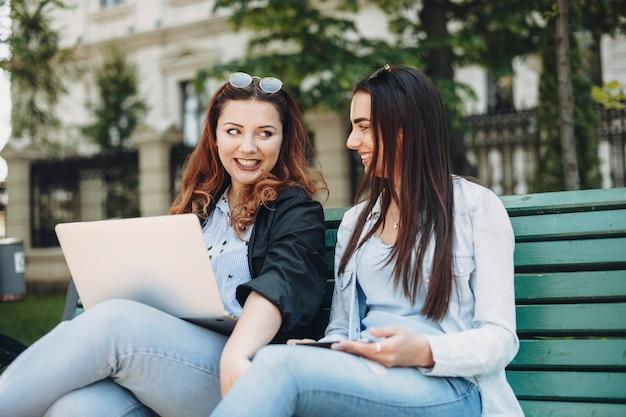 Mulheres ruivas segurando um laptop nas pernas, sentadas em um banco