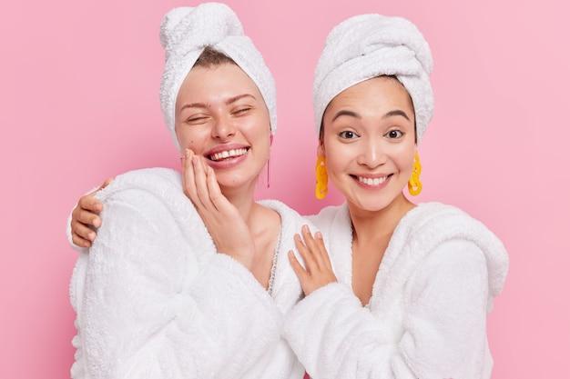 Mulheres se abraçam e sorriem alegremente se sentem renovadas, usam roupões de banho macios e toalhas na cabeça aproveitam os procedimentos do spa em casa isolado no rosa