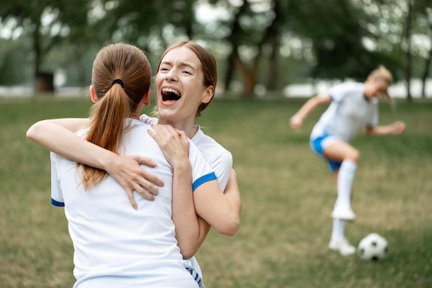 Mulheres se abraçando no campo de futebol