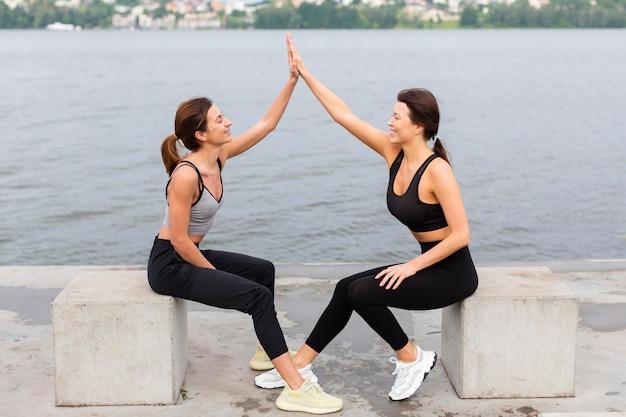 Mulheres se cumprimentando enquanto se exercitam ao ar livre