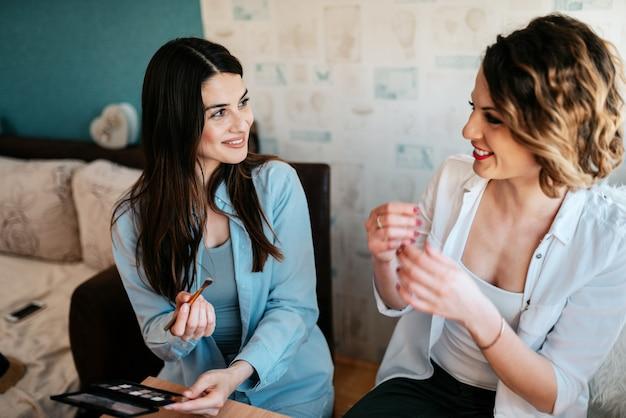 Mulheres se divertindo fazendo maquiagem dentro de casa.