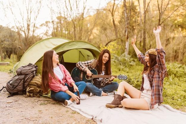 Mulheres se divertindo perto da tenda